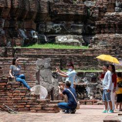 Un visitante posa para fotos en medio de las ruinas del complejo del templo Wat Mahathat del siglo XIV en la antigua capital de Ayutthaya, al norte de Bangkok, mientras las autoridades reabrieron los sitios a los turistas después de los bloqueos para detener la propagación de el nuevo coronavirus COVID-19. | Foto:Alex OGLE / AFP