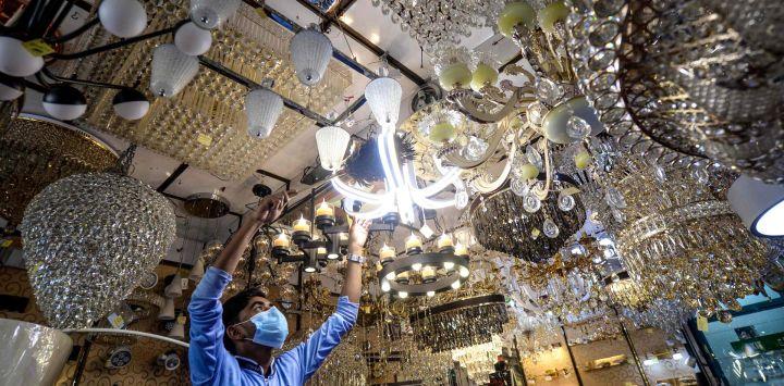 Un comerciante limpia el polvo de un candelabro en una tienda de luces en Dhaka.