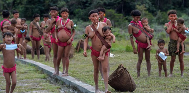 Los miembros del grupo étnico yanomami, algunos de ellos con máscaras faciales, se ven en un pelotón fronterizo especial, donde se realizan pruebas para COVID-19, en la tierra indígena de Surucucu, en Alto Alegre, Brasil.