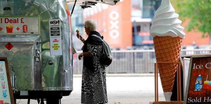 Una mujer compra un helado en Gabriel's Wharf junto al río Támesis en Londres. El gobierno ha estado suavizando las órdenes de quedarse en casa impuestas a fines de marzo con la reapertura de bares, restaurantes y museos este fin de semana.
