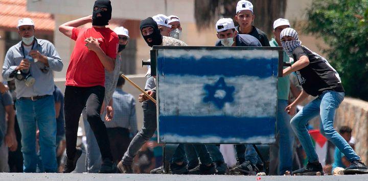 Los manifestantes palestinos, de pie detrás de un escudo pintado con los colores de la bandera israelí, arrojan piedras hacia las tropas israelíes (sin ser vistas) durante una manifestación en la aldea de Kfar Qaddum en Cisjordania.
