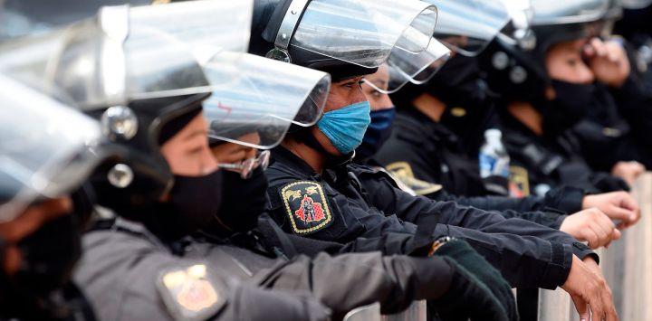 La policía antidisturbios espera mientras el personal médico de diferentes instituciones protesta contra el reciclaje de máscaras faciales en medio de la pandemia de coronavirus COVID-19 a lo largo de la Avenida Reforma en la Ciudad de México.
