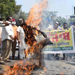 La Unión de Operadores de Taxi de Punjab grita consignas mientras queman una efigie del primer ministro de India, Narendra Modi, y el ministro en jefe de Punjab, Amarinder Singh, durante una protesta contra el gobierno central por las alzas de los precios de la gasolina y el diesel, en Amritsar. | Foto:NARINDER NANU / AFP