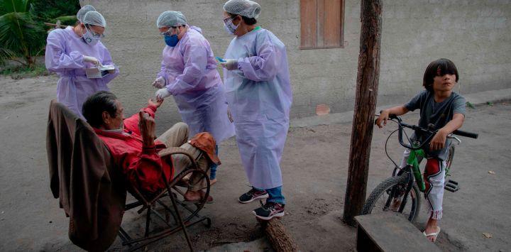Los profesionales de la salud administran las pruebas COVID-19 a un anciano indígena guaraní en el campamento de la tribu Sao Mata Verde Bonita, en tierra indígena guaraní, en Marica, estado de Río de Janeiro, Brasil.