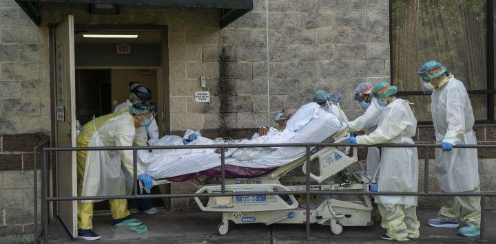 Los miembros del personal médico mueven una cama para transferir a un paciente a otra habitación fuera de la unidad de cuidados intensivos COVID-19 en el United Memorial Medical Center en Houston, Texas.