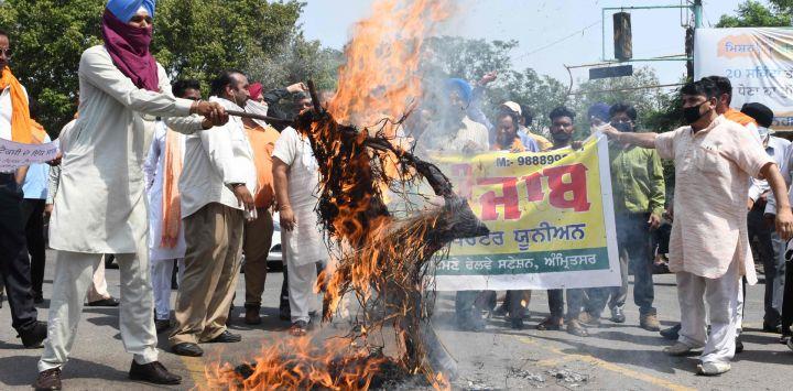 La Unión de Operadores de Taxi de Punjab grita consignas mientras queman una efigie del primer ministro de India, Narendra Modi, y el ministro en jefe de Punjab, Amarinder Singh, durante una protesta contra el gobierno central por las alzas de los precios de la gasolina y el diesel, en Amritsar.