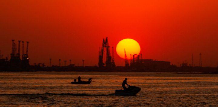 Un barco navega y un hombre monta una moto de agua a lo largo del río Shatt Al-Arab en la ciudad portuaria de Basora, en el sur de Iraq.