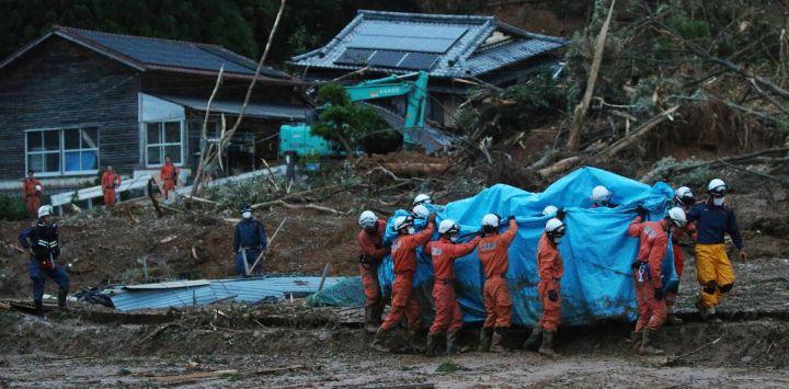Los bomberos llevan a una persona cubierta por una sábana azul en el sitio de un deslizamiento de tierra causado por las fuertes lluvias en Ashikita.