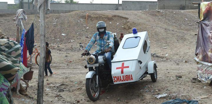 Un hombre conduce su sidecar de dos ruedas transformado en una ambulancia, en un barrio pobre de Ahmedabad.