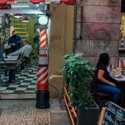 Un hombre se corta el cabello mientras la gente almuerza en un restaurante en Sao Paulo, Brasil, cuando los bares, restaurantes y salones de belleza de la ciudad reabrieron sus puertas después de más de tres meses de encierro para luchar contra el COVID. 19 pandemia de coronavirus. | Foto:NELSON ALMEIDA / AFP