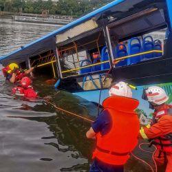 Los equipos de rescate trabajan después de que un autobús se hundiera en un lago en Anshun, en la provincia de Guizhou, suroeste de China. - Al menos 21 personas murieron cuando un autobús que transportaba estudiantes a su examen anual de ingreso a la universidad se hundió en un lago en el suroeste de China. | Foto:STR / AFP