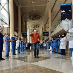 Hiroaki Fujita de Japón, el último paciente en el hospital temporal COVID-19 construido en el centro de Dubai en los Emiratos Árabes Unidos, saluda a las enfermeras y a los médicos cuando sale de las instalaciones. | Foto:GIUSEPPE CACACE / AFP