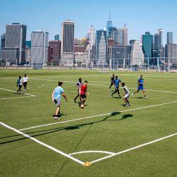 La gente juega fútbol frente al horizonte del Bajo Manhattan cuando la Ciudad de Nueva York comienza oficialmente la  | Foto:Johannes Eisele / AFP