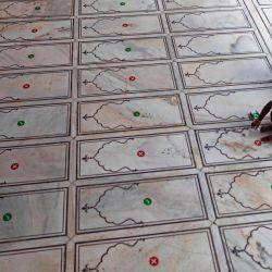 Un trabajador coloca una calcomanía en el piso para que los devotos mantengan el distanciamiento social durante las oraciones cuando la mezquita Jama Masjid se reabre después de que el gobierno alivió un bloqueo nacional impuesto como medida preventiva contra la propagación del coronavirus COVID-19, en los barrios antiguos de Nueva Delhi. | Foto:XAVIER GALIANA / AFP