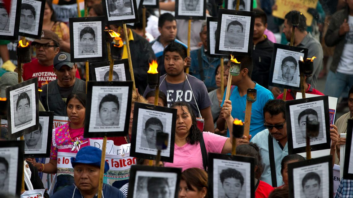 In this April 26, 2016 file photo, family members and supporters of 43 missing teachers college students carry pictures of the students as they march to demand the case not be closed and that experts' recommendations about new leads be followed, in Mexico City.