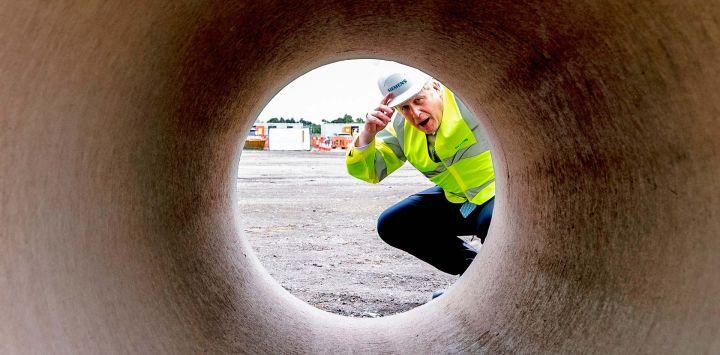 El primer ministro británico, Boris Johnson, mira hacia abajo un tubo de gran diámetro durante una visita al sitio de construcción de la fábrica de ferrocarriles de Siemens en Goole, noreste de Inglaterra.