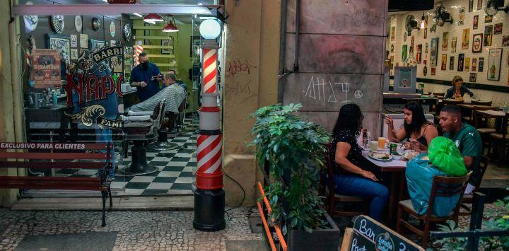 Un hombre se corta el cabello mientras la gente almuerza en un restaurante en Sao Paulo, Brasil, cuando los bares, restaurantes y salones de belleza de la ciudad reabrieron sus puertas después de más de tres meses de encierro para luchar contra el COVID. 19 pandemia de coronavirus.