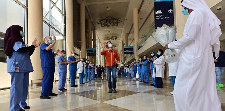 Hiroaki Fujita de Japón, el último paciente en el hospital temporal COVID-19 construido en el centro de Dubai en los Emiratos Árabes Unidos, saluda a las enfermeras y a los médicos cuando sale de las instalaciones.