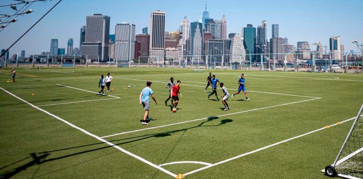 La gente juega fútbol frente al horizonte del Bajo Manhattan cuando la Ciudad de Nueva York comienza oficialmente la