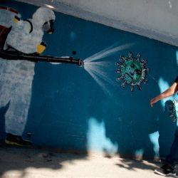 Una mujer camina frente a un mural que representa a un hombre en traje protector rociando desinfectante, en el barrio de Tijuca en Río de Janeiro, Brasil.   Foto:MAURO PIMENTEL / AFP