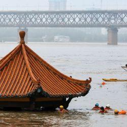 La gente nada en el río Yangtze hinchado mientras se ve el techo de un pabellón inundado sobre las aguas de Wuhan en la provincia central de Hubei de China.   Foto:STR / AFP