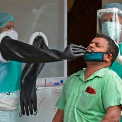 Los funcionarios de salud recolectan una muestra de hisopo de un hombre para analizar el coronavirus COVID-19, en un centro de análisis detrás de un área abierta de un Hospital de Ojos Sarojini Devi administrado por el gobierno, en Hyderabad.   Foto:NOAH SEELAM / AFP