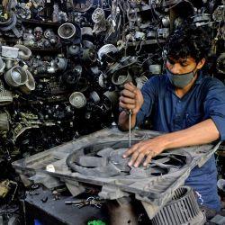 Un trabajador repara un ventilador en un mercado de repuestos de automóviles de segunda mano después de que el gobierno alivió un bloqueo nacional impuesto como medida preventiva contra la propagación del coronavirus COVID-19, en Chennai.   Foto:Arun Sankar / AFP