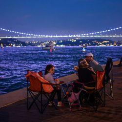 La gente disfruta de la noche mientras se sientan junto a la orilla del Bósforo mientras el puente Fatih Sultan Mehmet se ve en el fondo en Estambul.   Foto:Ozan Kose / AFP