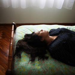 "Camila Fernández poses for a photo on her bed during the government-ordered lockdown to curb the spread of the coronavirus, in Buenos Aires, Monday, June 29, 2020. The 26-year-old, who works at a prosecutor's office, lives alone in her apartment in the company of books, of which she has read more than 20 during quarantine, while studying to become a public translator and English teacher. ""Quarantine is an ideal state,"" said Fernández."