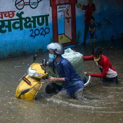 Los automovilistas se abren camino a través de una calle inundada después de las fuertes lluvias en Allahabad. | Foto:SANJAY KANOJIA / AFP