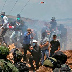 Los manifestantes palestinos y las fuerzas israelíes se enfrentan durante una protesta contra los asentamientos judíos y la anexión planificada de partes de la Cisjordania ocupada por Israel, en la ciudad de Asira Shamaliya, cerca de la ciudad cisjordana de Naplusa. | Foto:ABBAS MOMANI / AFP