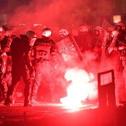 La policía se paró alrededor de una llamarada en llamas afuera del edificio de la Asamblea Nacional en Belgrado, durante enfrentamientos con manifestantes en una manifestación contra un toque de queda de fin de semana anunciado para combatir el resurgimiento de las infecciones por COVID-19. | Foto:ANDREJ ISAKOVIC / AFP
