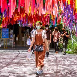 Una mujer con una máscara facial sale de un centro comercial en Bangkok. | Foto:Mladen Antonov / AFP