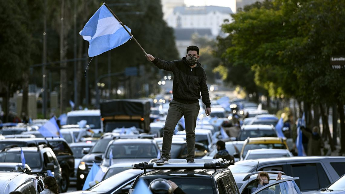 A man waves the Argentine flag during a protest against President Alberto Fernández health policies and the tightened virus lockdown measures against the spread of the Covid-19 coronavirus, in Buenos Aires on July 9, 2020.