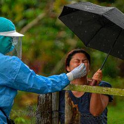 Un trabajador de salud recolecta una muestra de hisopo nasal para analizar COVID-19 a un residente, en el distrito de Arraijan, a 23 km al oeste de la ciudad de Panamá. | Foto:Luis Acosta / AFP