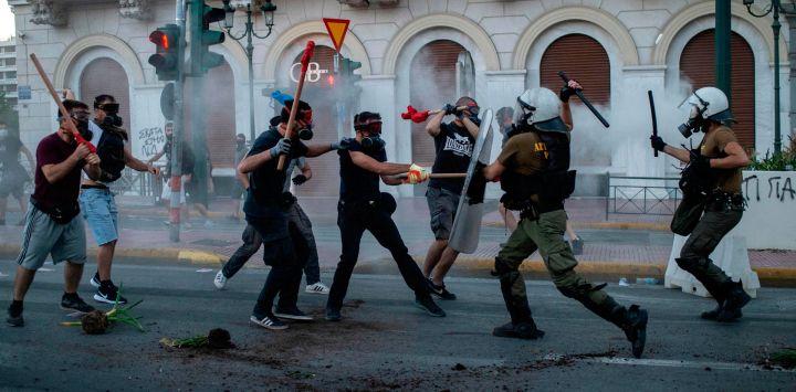 Los manifestantes se enfrentan con la policía antidisturbios durante una manifestación frente al parlamento para protestar contra la próxima ley del gobierno conservador para controlar las manifestaciones, en Atenas.