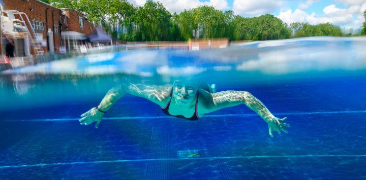 Un nadador se mueve bajo el agua en el Parlamento Hill Lido en Londres, ya que las restricciones se alivian aún más durante la nueva pandemia de coronavirus COVID-19. - Inaugurado en 1938, Parliament Hill Lido, en el norte de Londres, es una piscina al aire libre sin calefacción, abierta al público los 365 días del año.