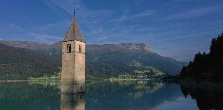 Una fotografía aérea tomada en la nueva ciudad de Curon Venosta (Graun im Vinschgau), a unos 100 km al noroeste de Bolzano, en el norte de Italia, muestra el campanario de la antigua iglesia de la ciudad de Curon sumergida en el lago Resia.