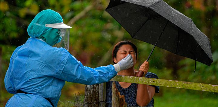Un trabajador de salud recolecta una muestra de hisopo nasal para analizar COVID-19 a un residente, en el distrito de Arraijan, a 23 km al oeste de la ciudad de Panamá.