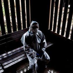 Un trabajador de la salud con un traje de protección contra la propagación del nuevo coronavirus COVID-19, descansa en un centro de salud en un barrio de bajos ingresos en San José. | Foto:Ezequiel Becerra / AFP