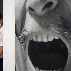 Un hombre con una máscara facial se encuentra junto a un retrato del artista español Salvador Dalí el día de la reapertura del museo Salvador Dalí en Figueras, después de estar cerrado durante más de tres meses debido a la nueva pandemia de coronavirus. | Foto:LLUIS GENE / AFP