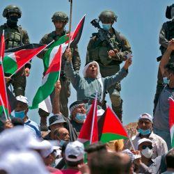 Los manifestantes, vestidos con máscaras y guantes de látex, ondean banderas palestinas mientras las fuerzas israelíes están en guardia cerca durante una protesta contra los asentamientos judíos y la anexión planificada de partes de la Cisjordania ocupada por Israel, en la ciudad de Asira Shamaliya, cerca de la ciudad de Cisjordania. | Foto:ABBAS MOMANI / AFP