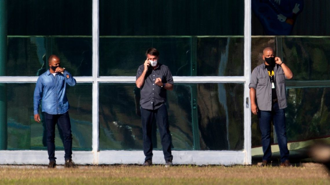 Brazil's President Jair Bolsonaro, centre, talks on his phone while standing outside his official Alvorada Palace residence, in Brasilia, Friday, July 10, 2020.