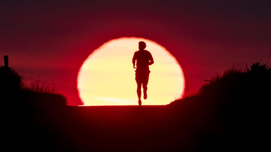 A man runs on a small path as the sun rises in Frankfurt, Germany.