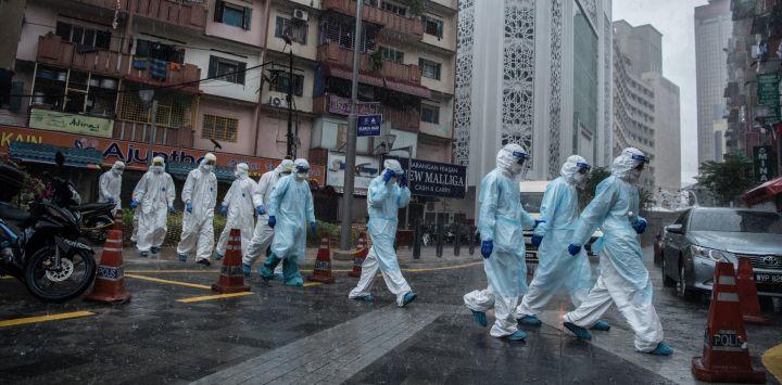 Malasia, Johannesburgo: los empleados del Ministerio de Salud abandonan un edificio después de evaluar a los residentes para detectar el coronavirus.