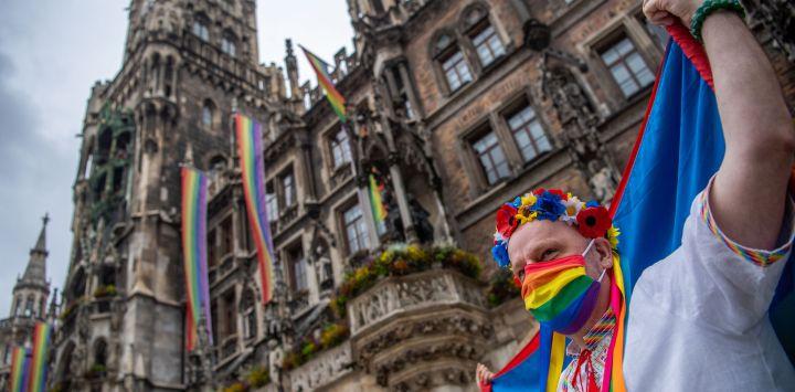 Un miembro de MunichKyivQueer sostiene la bandera del orgullo del arco iris durante una manifestación en conmemoración del Día de Christopher Street en Múnich. El desfile anual de orgullo de Christopher Street Day se cancela este año debido a la pandemia de Coronavirus; en cambio, pequeños grupos salieron a las calles para demostrar y celebrar el día mientras se realizaba una transmisión en vivo con música y debates.