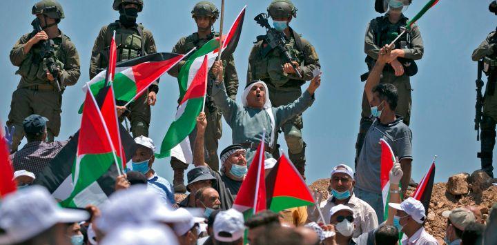Los manifestantes, vestidos con máscaras y guantes de látex, ondean banderas palestinas mientras las fuerzas israelíes están en guardia cerca durante una protesta contra los asentamientos judíos y la anexión planificada de partes de la Cisjordania ocupada por Israel, en la ciudad de Asira Shamaliya, cerca de la ciudad de Cisjordania.