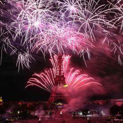 Los fuegos artificiales explotan sobre la Torre Eiffel como parte de las celebraciones anuales del Día de la Bastilla en París. | Foto:Anne-Christine Poujoulat / AFP