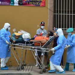 El personal de salud de la Comisión Permanente de Contingencia de Honduras (COPECO) ayuda a un hombre que muestra síntomas del nuevo coronavirus, COVID-19, en Tegucigalpa. | Foto:Orlando Sierra / AFP