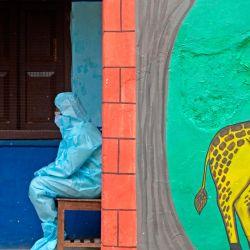 Un trabajador de la salud con equipo de protección personal (PPE) se sienta a la entrada de un centro de pruebas gratuito para el coronavirus COVID-19, en una escuela primaria del gobierno en Secunderabad, la ciudad gemela de Hyderabad. | Foto:NOAH SEELAM / AFP